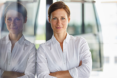 Portrait of smiling businesswoman leaning at glass pane in office - p300m2012972 von Rainer Berg