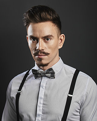 Portrait of confident young man wearing suspenders over gray background - p301m1579838 by Alexandr Sherstobitov