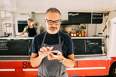 Owner using mobile phone against street food truck - p426m1114872f by Maskot