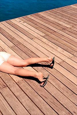Beine einer Frau auf Badesteg - p9790756 von Frei_Photography