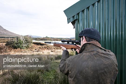 Hunter taking aim with a shotgun - p1082m2022018 by Daniel Allan
