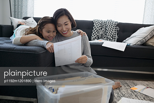 Mother and daughter viewing financial paperwork in living room - p1192m1201890 by Hero Images