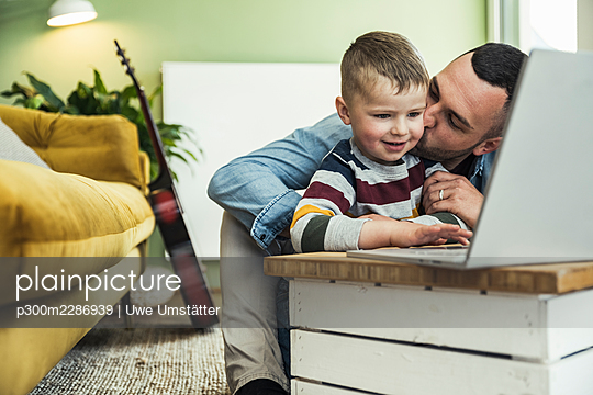 Father kissing son using laptop in living room at home - p300m2286939 by Uwe Umstätter