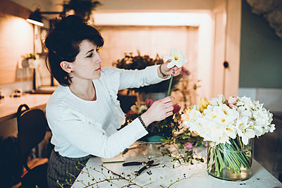Side view of florist arranging daffodils in vase at flower shop - p1166m1474267 by Cavan Images