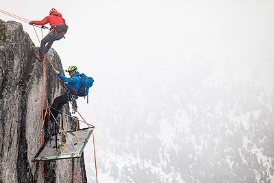 Climbers rappelling onto portaledge on a vertical cliff face. - p1166m2212659 by Cavan Images