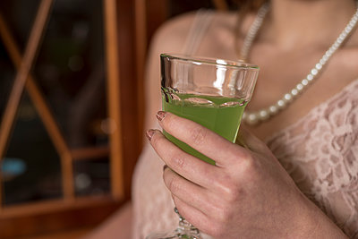 Young 1920s style female in delicate dress holding a glass of absinthe. - p1433m1531945 by Wolf Kettler