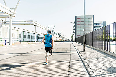 Young athlete jogging in the city - p300m2013117 by Uwe Umstätter