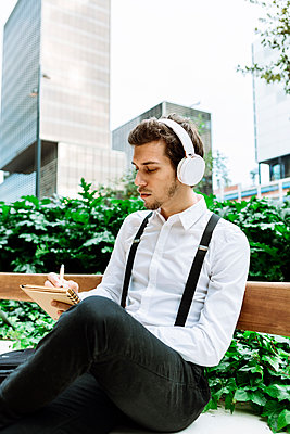 Young businessman with headphones sitting on bench outdoors and writing in notepad - p300m2241862 by Xavier Lorenzo
