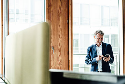 Smiling senior businessman using smart phone while standing against glass window in office - p300m2266313 by Gustafsson