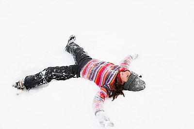 Girl making snow angel - p42913558f by Brigitte Sporrer