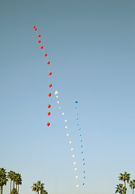 Rows of red, white and blue balloons floating against blue sky, USA - p429m1494663 by Seb Oliver