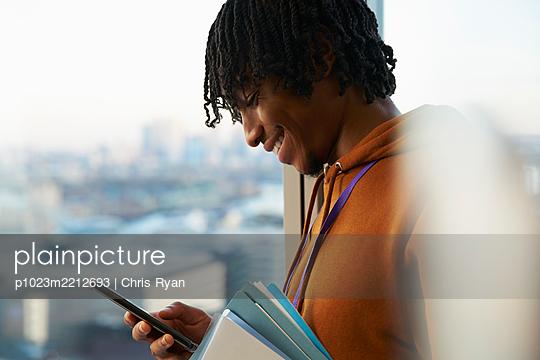Smiling businessman using smart phone at window - p1023m2212693 by Chris Ryan