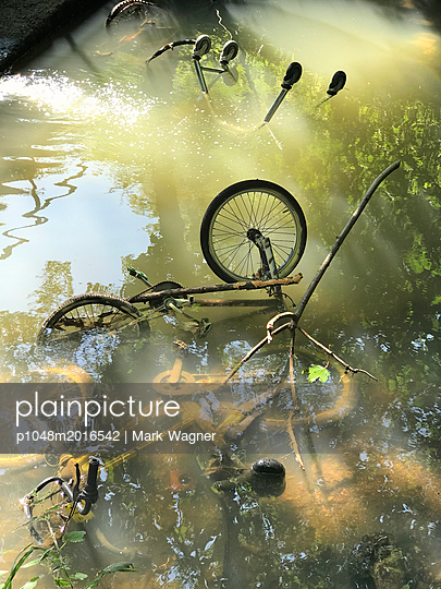 Bicycles and trolley dumped in river - p1048m2016542 by Mark Wagner