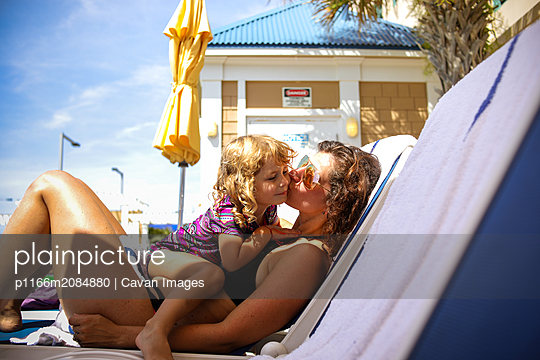 mom and little girl on lounge chair in bathing suits giving kiss - p1166m2084880 by Cavan Images