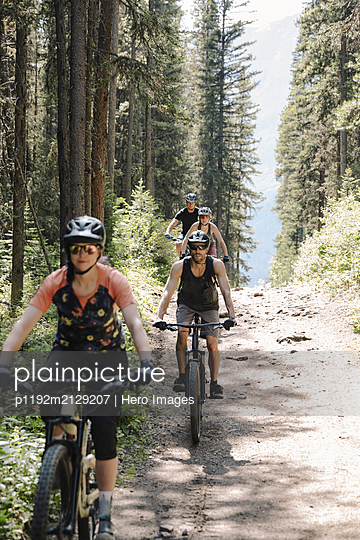 Friends mountain biking on trail in sunny woods - p1192m2129207 by Hero Images