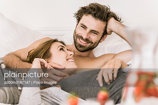 Happy young couple lying in bed - p300m2167147 by Floco Images