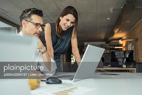 Male and female professionals using laptop while working in office - p300m2294197 by Uwe Umstätter