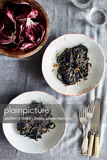 Overhead view of squid ink spaghetti dish and radicchio lettuce in bowl - p429m1418486 by Debby Lewis-Harrison