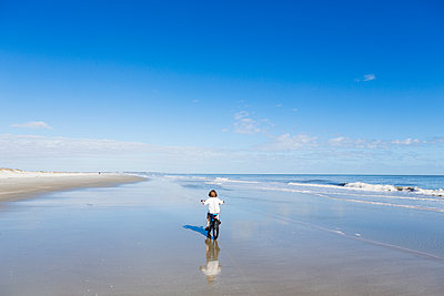 A young boy biking on a sandy beach   - p1100m2164913 by Mint Images