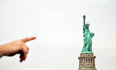 Cropped hand pointing towards Statue Of Liberty against clear sky - p1166m1546428 by Cavan Social