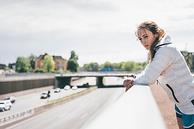 Sportive young woman leaning on railing at motorway - p300m2005528 von Kniel Synnatzschke