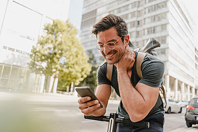Casual man with e-scooter checking smartphone  in the city - p300m2170438 by Kniel Synnatzschke