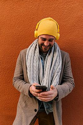 Valencia, Spain. Elegant young man, with headphones, on a red wall background. - p300m2251659 von Ezequiel Giménez