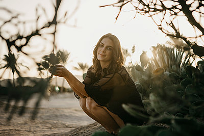 Smiling woman with sand crouching by cactus plant during sunset - p300m2256125 by letizia haessig photography