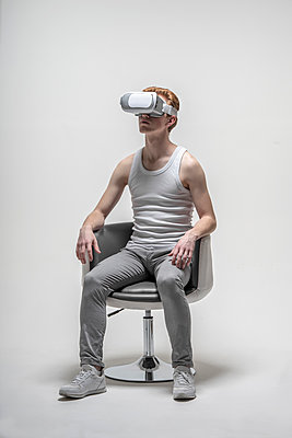 Young man using virtual reality simulator glasses - p301m2018426 by Vasily Pindyurin