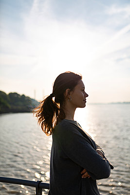 Young woman looks out over the Elbe river - p341m2210412 by Mikesch