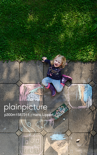 Smiling little girl drawing with chalk outdoors, top view - p300m1587311 von Hans Lippert