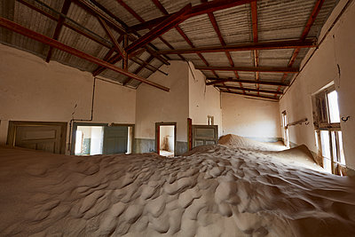 Interior of an abandoned building full of sand. - p1100m1489990 by Mint Images