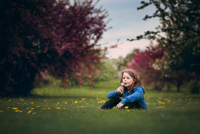 Girl blowing dandelion flower while sitting on grassy field at park - p1166m1509123 by Cavan Images