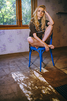 Blond woman sitting on the wooden chair at her rural house - p1577m2220125 by zhenikeyev