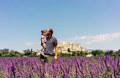 France, Grignan, father kissing his little daughter in lavender field - p300m2069846 by Gemma Ferrando
