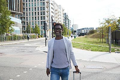 Smiling businessman walking on street in city - p300m2241572 von Pete Muller
