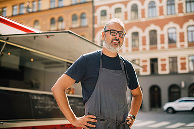 Portrait of confident chef standing by food truck on street in city - p426m1114876f by Maskot