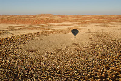Shadow of hot air balloon over desert - p555m1479698 by Chris Sattlberger