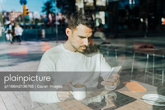 Smiling young man working in a cafe looking at cell phone - p1166m2136765 by Cavan Images