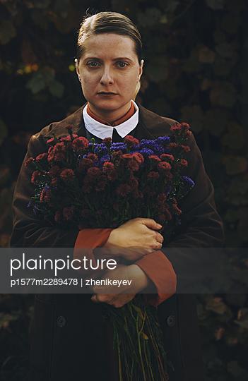 Retro styled woman holding bunch of wildflowers - p1577m2289478 by zhenikeyev