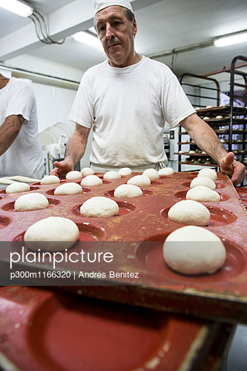 Doughs in hamburger bread molds before baking in a bakery - p300m1166320 by Andrés Benitez