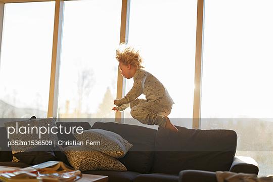 plainpicture | Photo library for authentic images - plainpicture p352m1536509 - Boy jumping on sofa - plainpicture/Folio Images/Christian Ferm