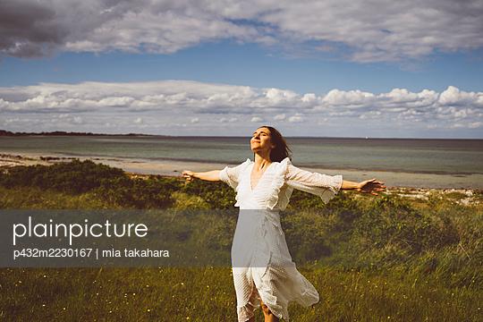Frau genießt die Stimmung am Meer - p432m2230167 von mia takahara