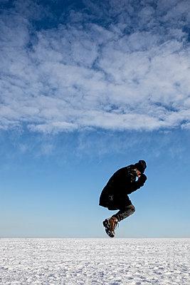 Mann springt auf dem Schneefeld - gekauert - p1212m1109016 von harry + lidy