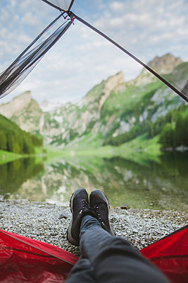 Woman's feet sticking out of tent by Seealpsee lake in Appenzell Alps, Switzerland - p1427m2146898 by Oleksii Karamanov