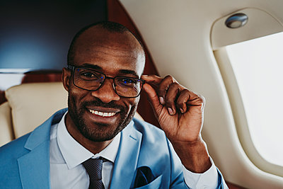 Happy male entrepreneur with eyeglasses in airplane - p300m2256369 by OneInchPunch
