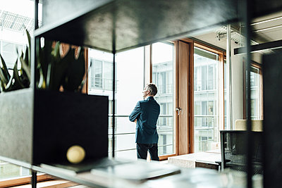 Businessman looking through glass window in office - p300m2265674 by Gustafsson