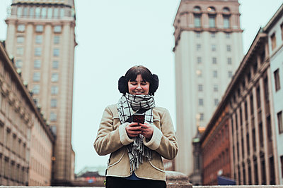 Smiling young woman wearing warm clothing while using mobile phone against buildings in city - p426m2088855 by Maskot