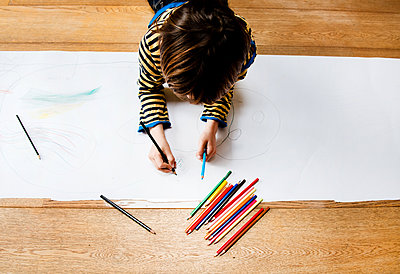 Overhead view of boy lying on floor drawing on long paper - p429m1407979 by Bonfanti Diego