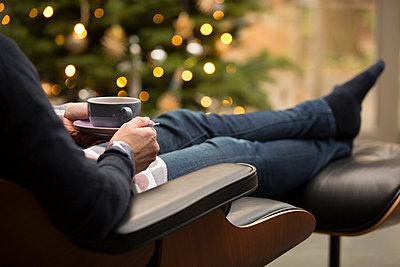 Frau hält Teetasse in der Hand und sitzt vor dem Weihnachtsbaum im Sessel. - p948m2014774 von Sibylle Pietrek